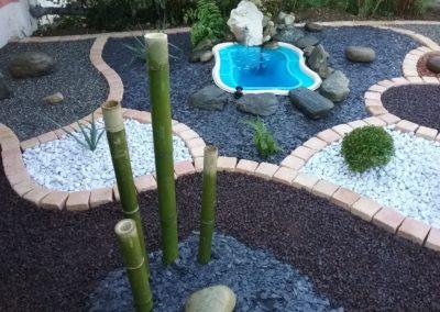 un massif zen avec des bambous, un petit bassin d'eau